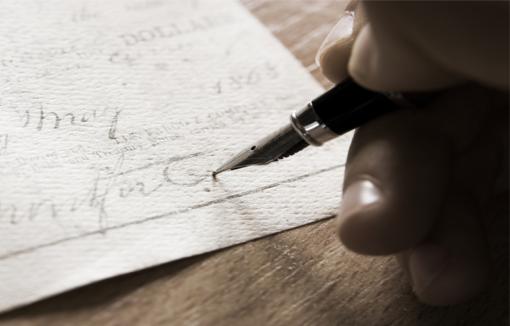 Hand mit Füllfederhalter schreibt auf einen Postscheck