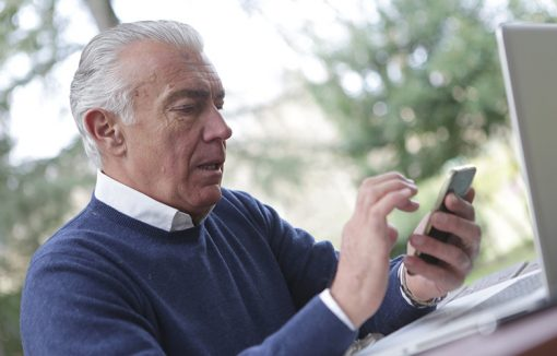 Senior mit Mobiltelefon und Laptop